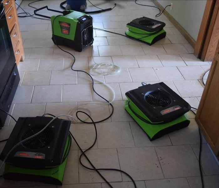 White tile floor in a kitchen with air movers and a dehumidifier placed strategically to dry the water