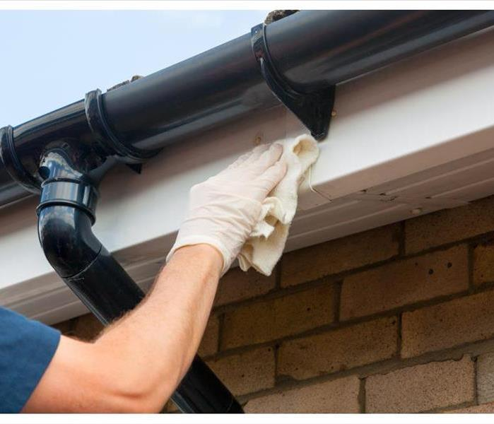Man cleaning and maintaining plastic guttering on a house