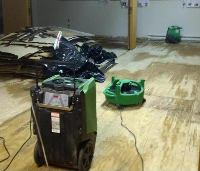 wet wooden floor, drying equipment placed in area